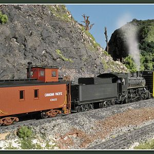USRA 0-6-0 shoves boxcars toward a natural rock tunnel portal
