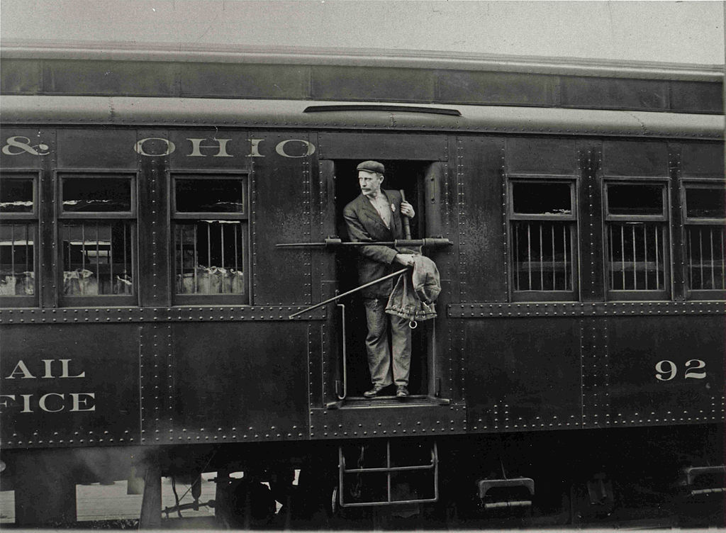 1024px-Railway_Post_Office_Clerk_in_Mail_Car.jpg